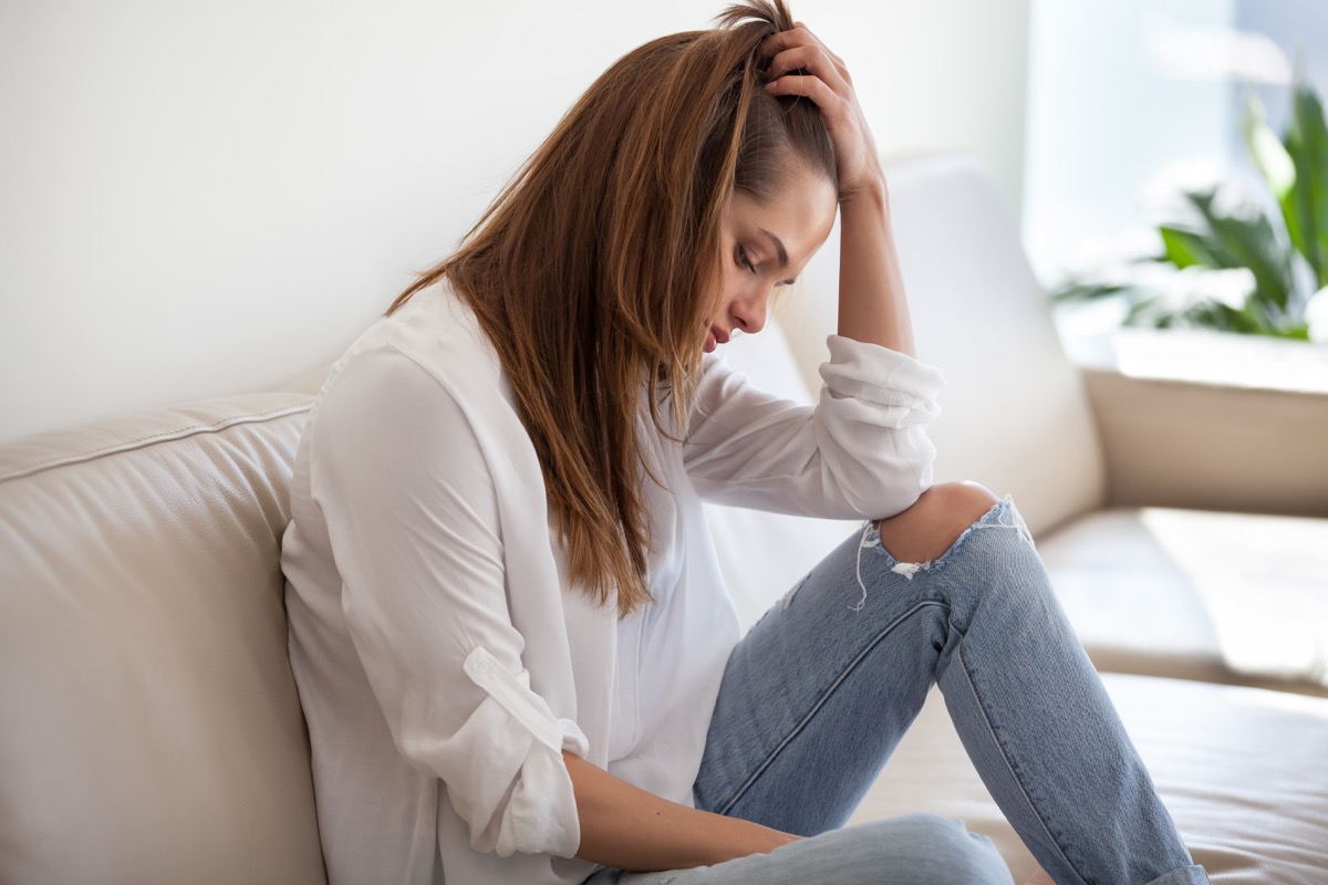 Woman is sad and depressed on the couch