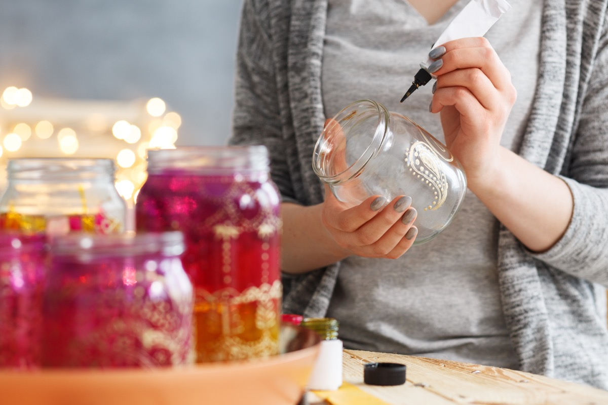woman completing diy project with mason jars