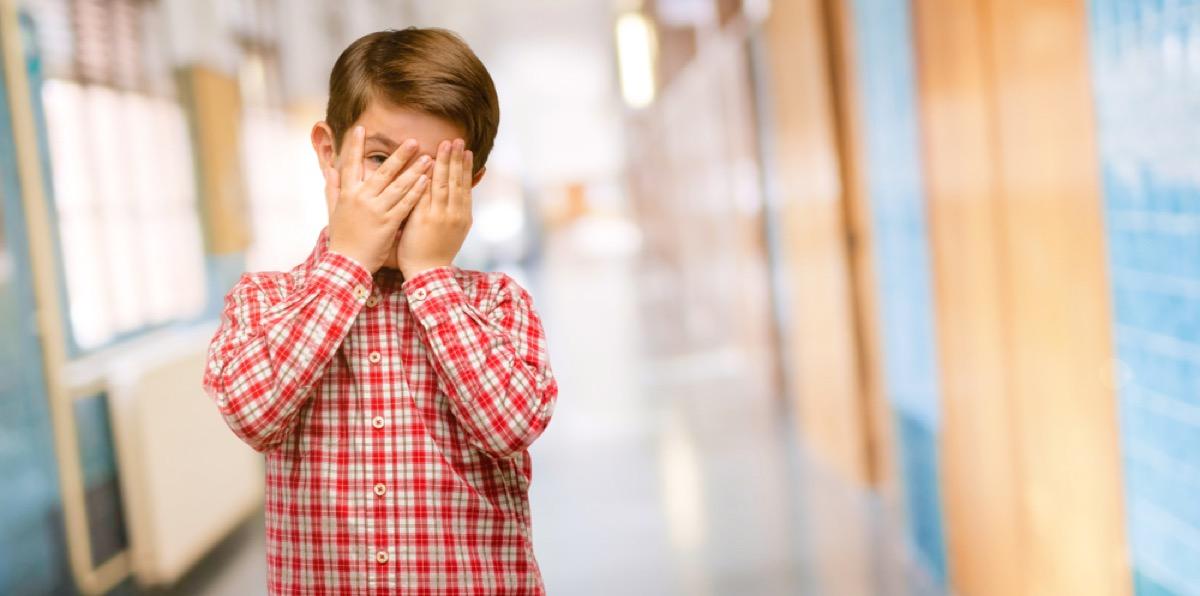 boy covers face in embarrassment in school hallway
