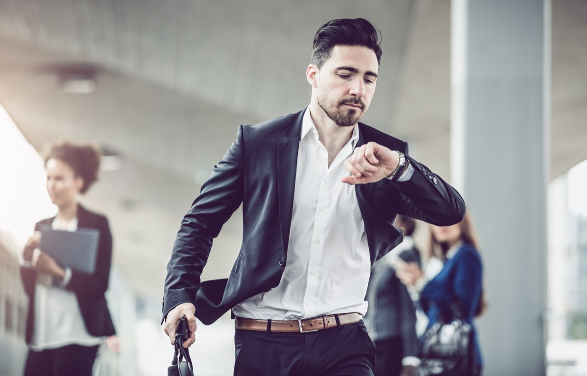 Businessman walking fast and checking the Time
