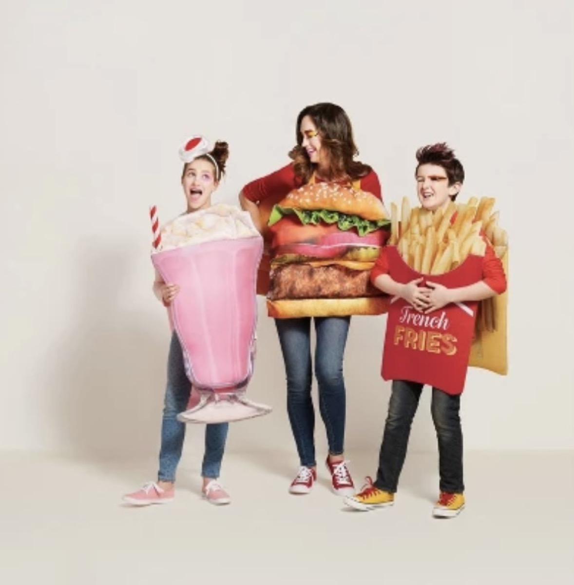 woman dressed as a hamburger, girl dressed as pink milkshake, and boy dressed as french fries, family halloween costumes