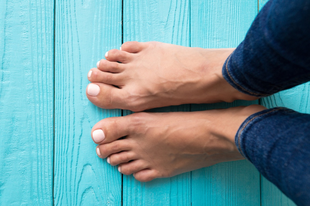 Woman's feet on wooden floor view from above.