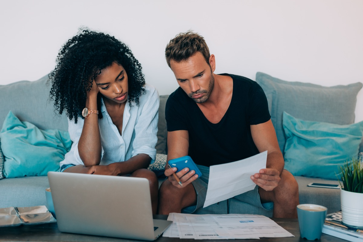 frustrated couple looking at their bills