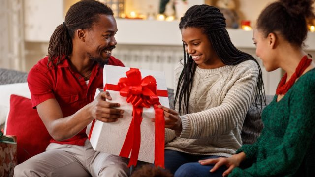 Man giving a Christmas present to his grateful friend or girlfriend