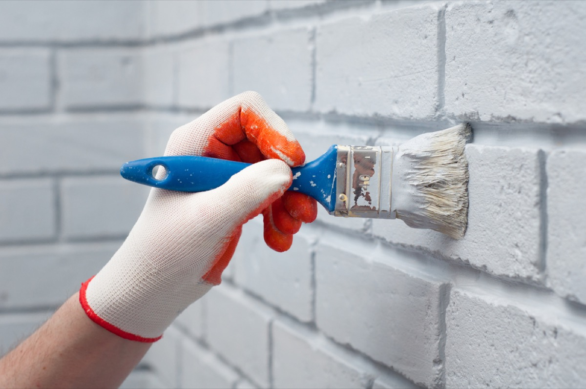 gloved hand painting brick white