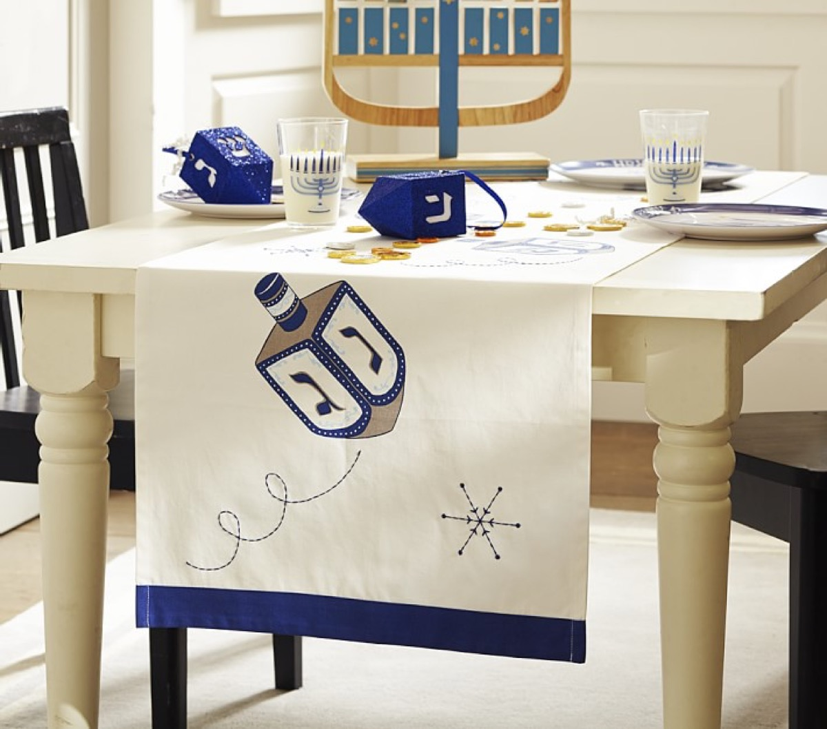 white table runner with dreidel on it and menorahs on the table, hanukkah decorations