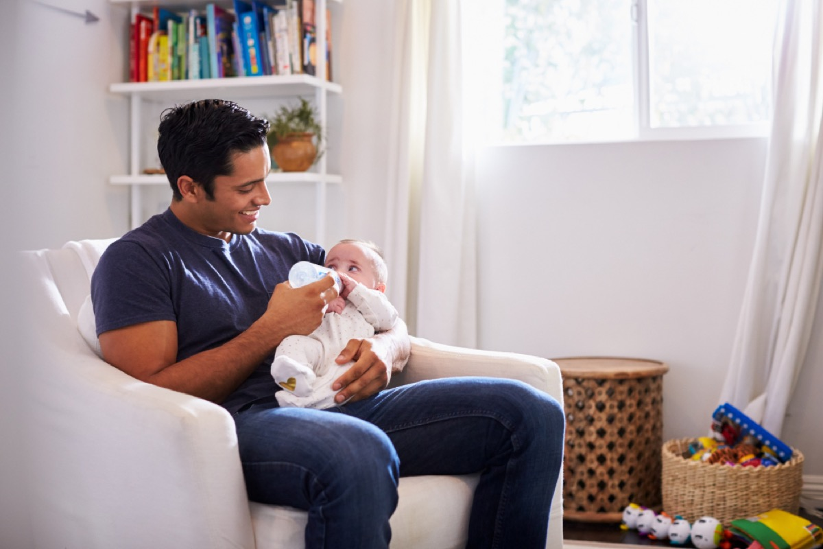 hispanic man holding baby on lap and feeding them with a bottle in a white room