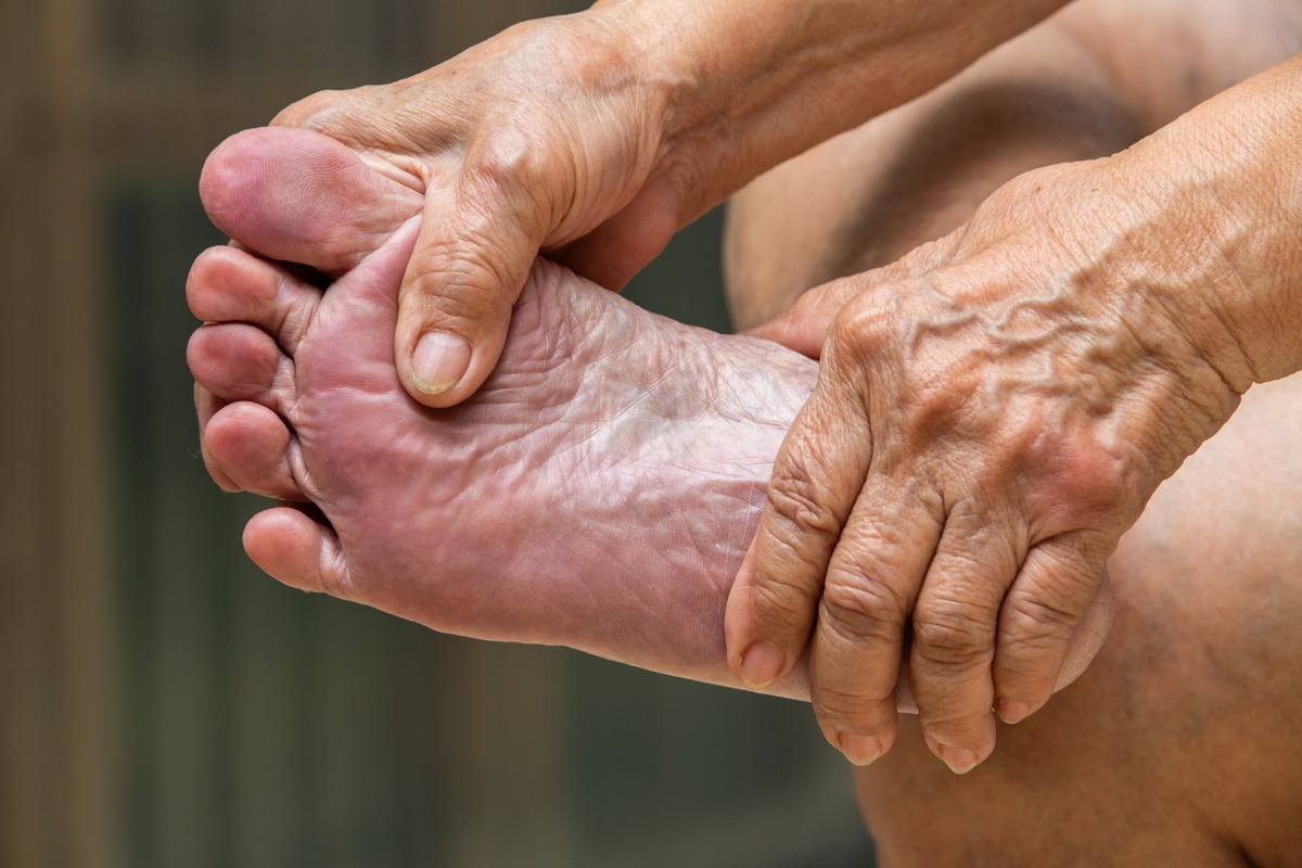 Senior woman's hands massaging her foot