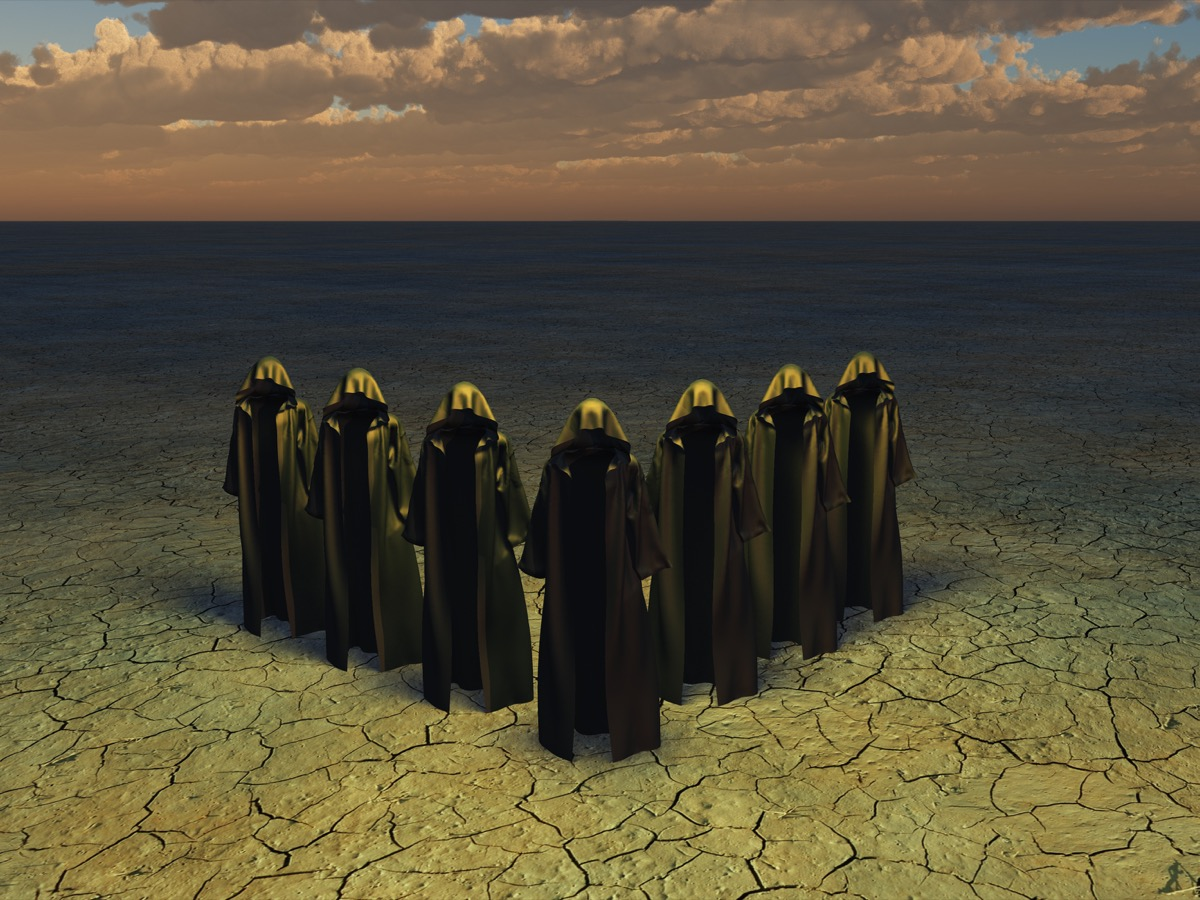 hooded figures on barren landscape