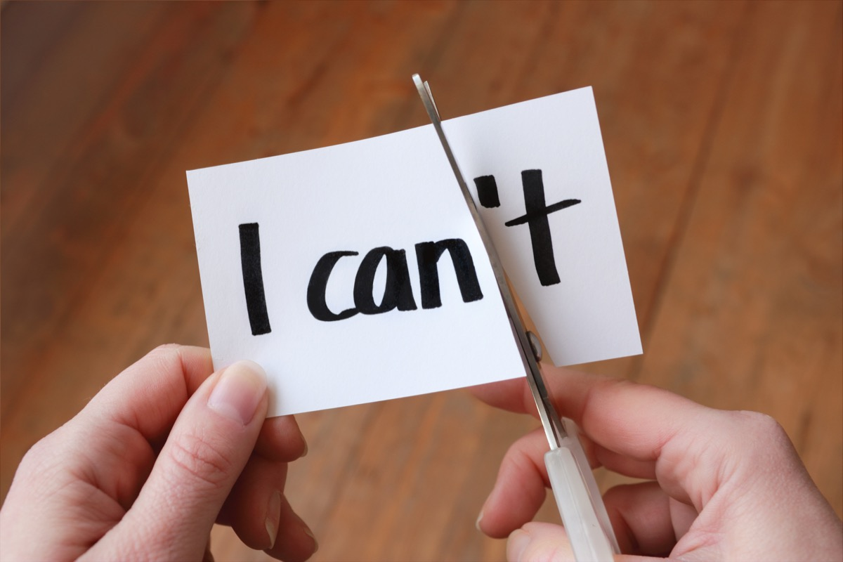 """hands shown cutting paper with scissors that reads """"i can't"""" so that it becomes """"i can"""""""
