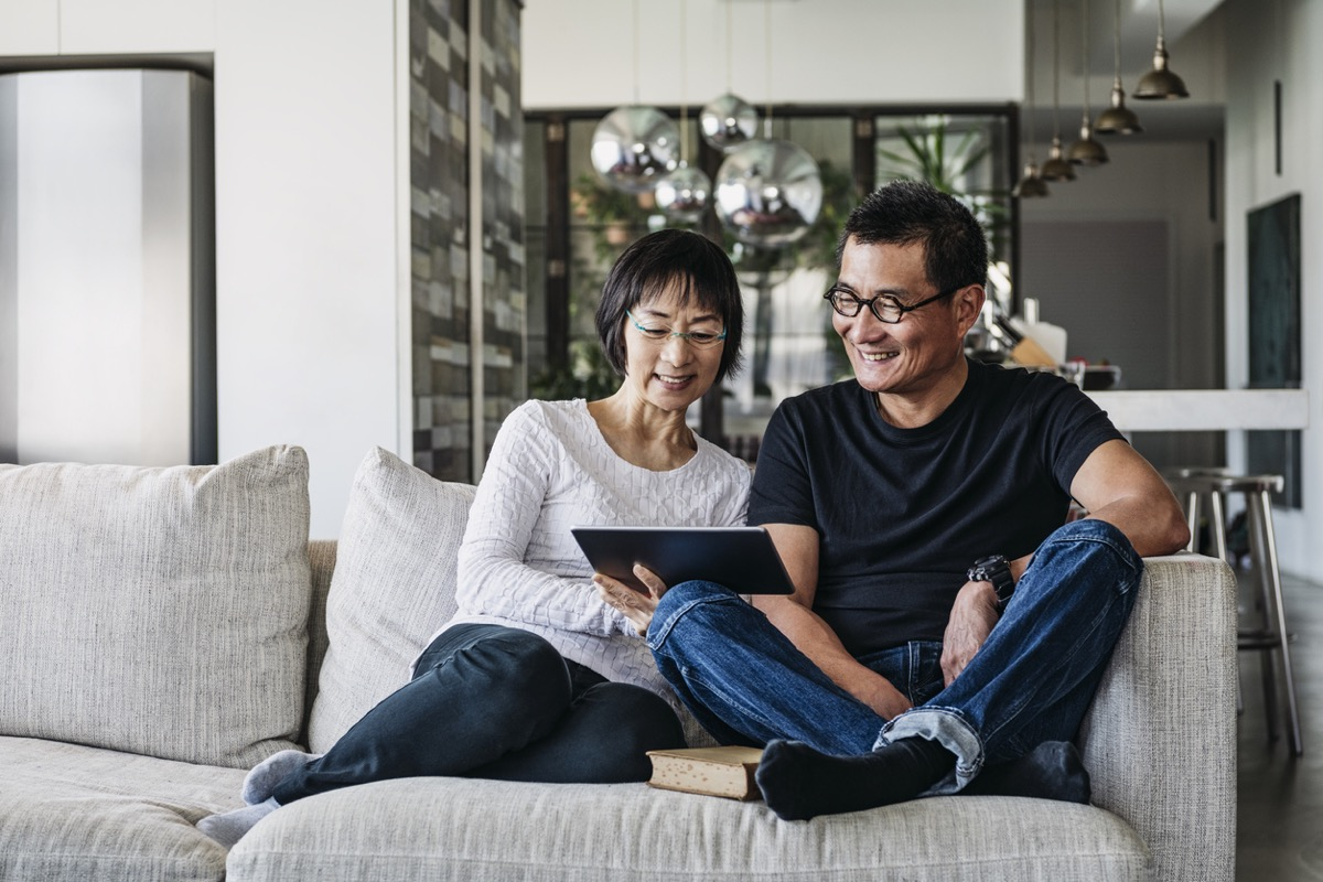 older asian man and woman on couch looking at a tablet together