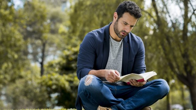 young latino man reading a book by himself in the park