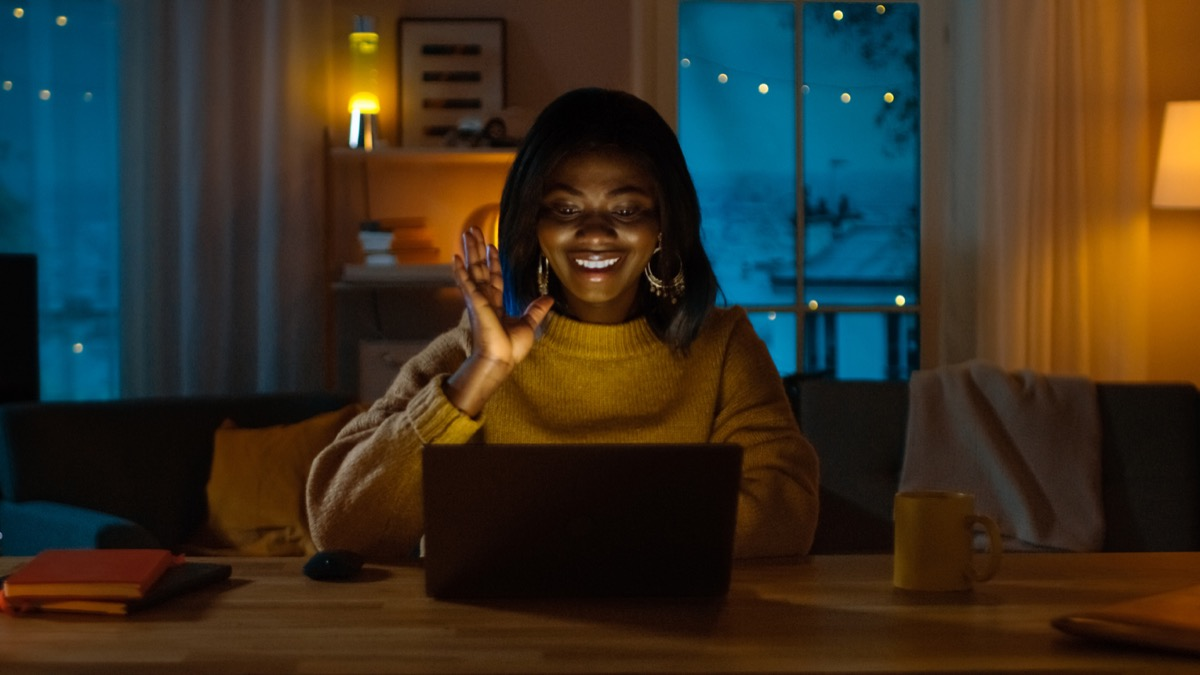 young black woman waving at her computer while videochatting at night