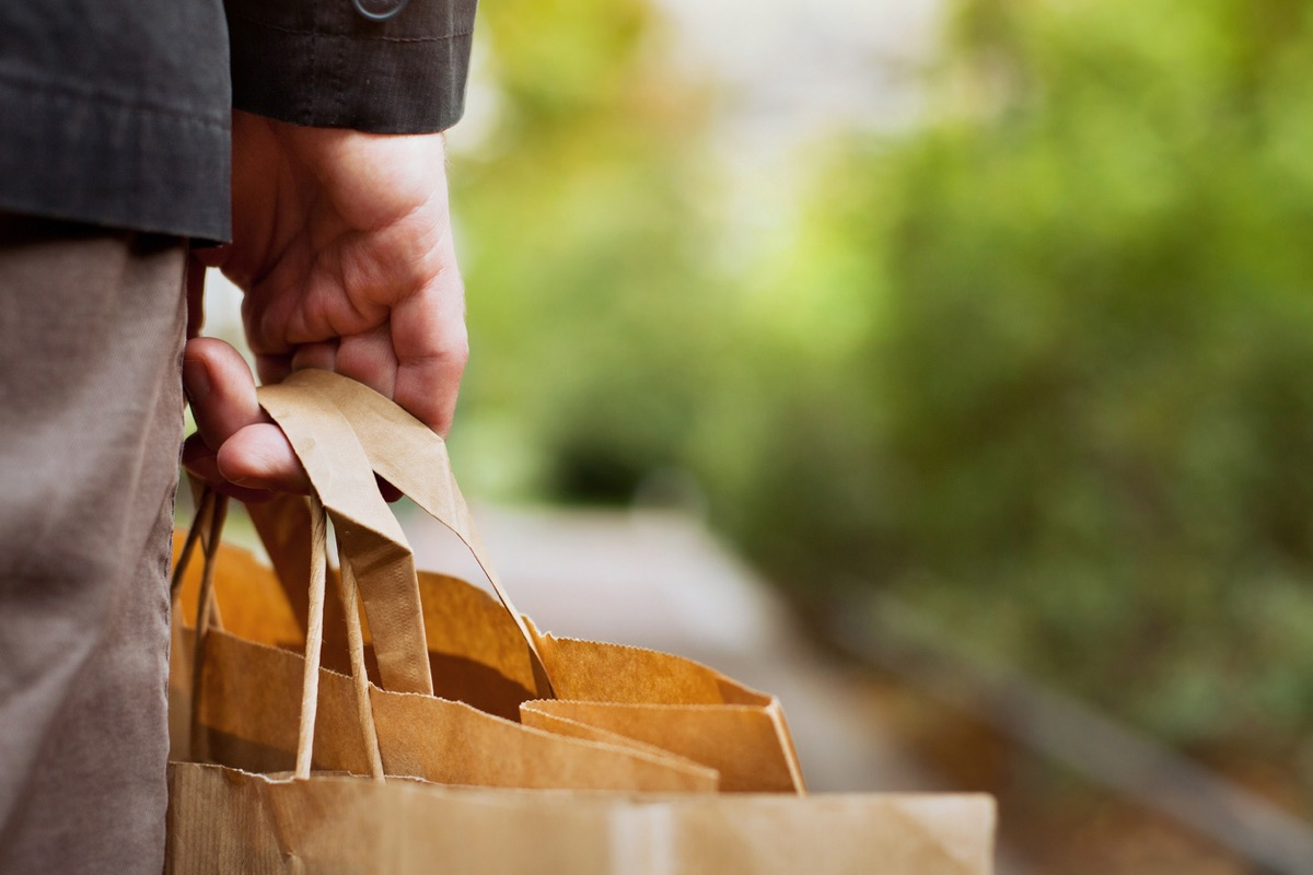 close up of man's hand holding the handle of a paper grocery bag