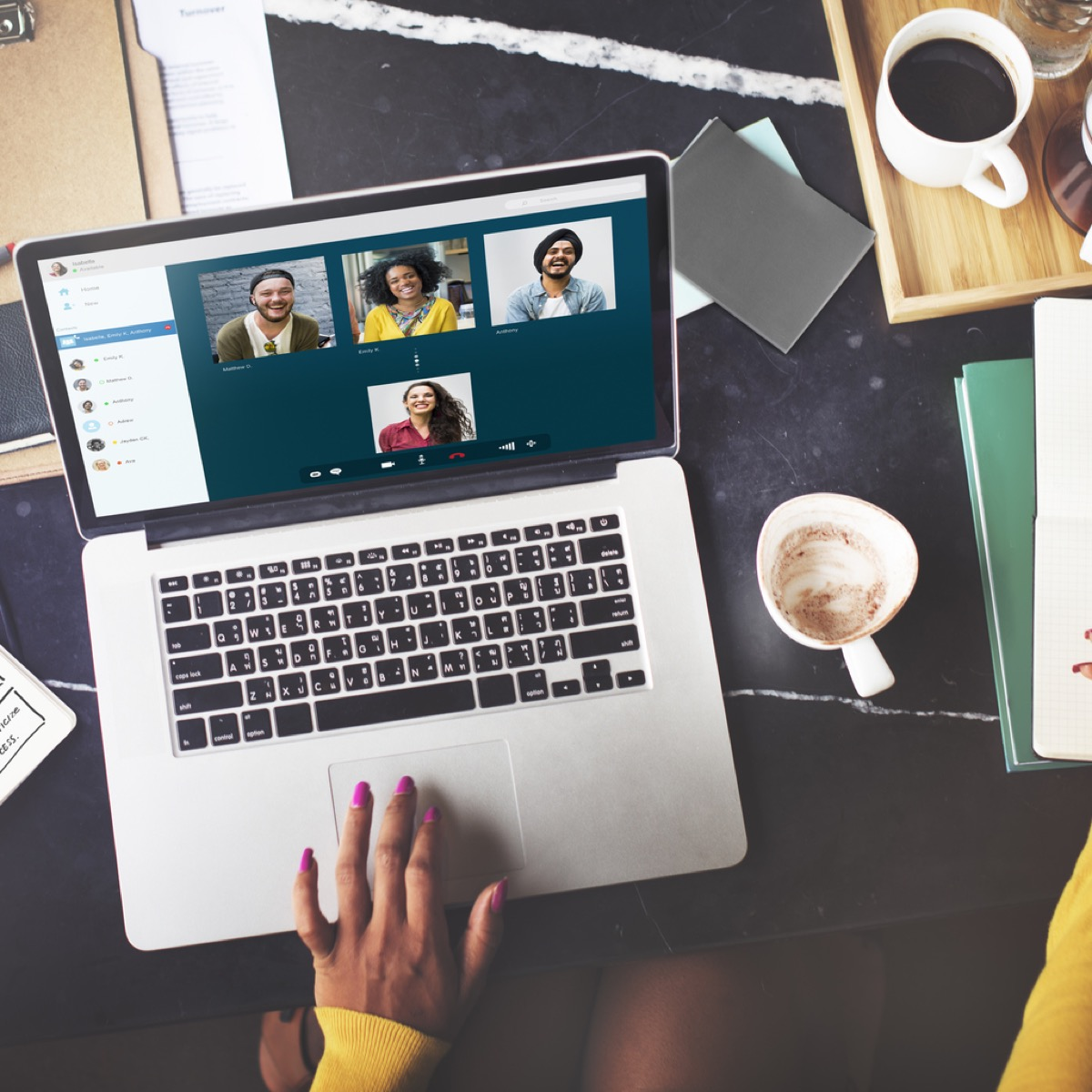 close up of woman's hand on computer while video chatting with four other people