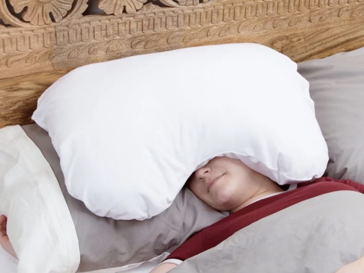 woman with white pillow on her head, better sleep essentials