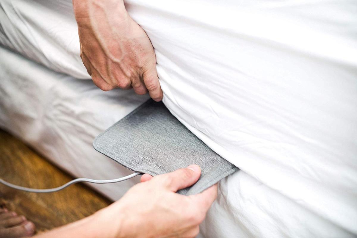 man tucking gray sleep tracker under mattress, better sleep essentials
