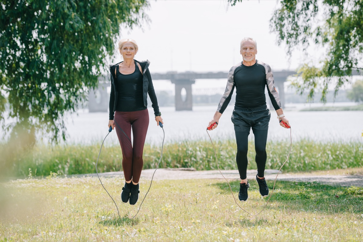 Two adults doing jump rope in the park