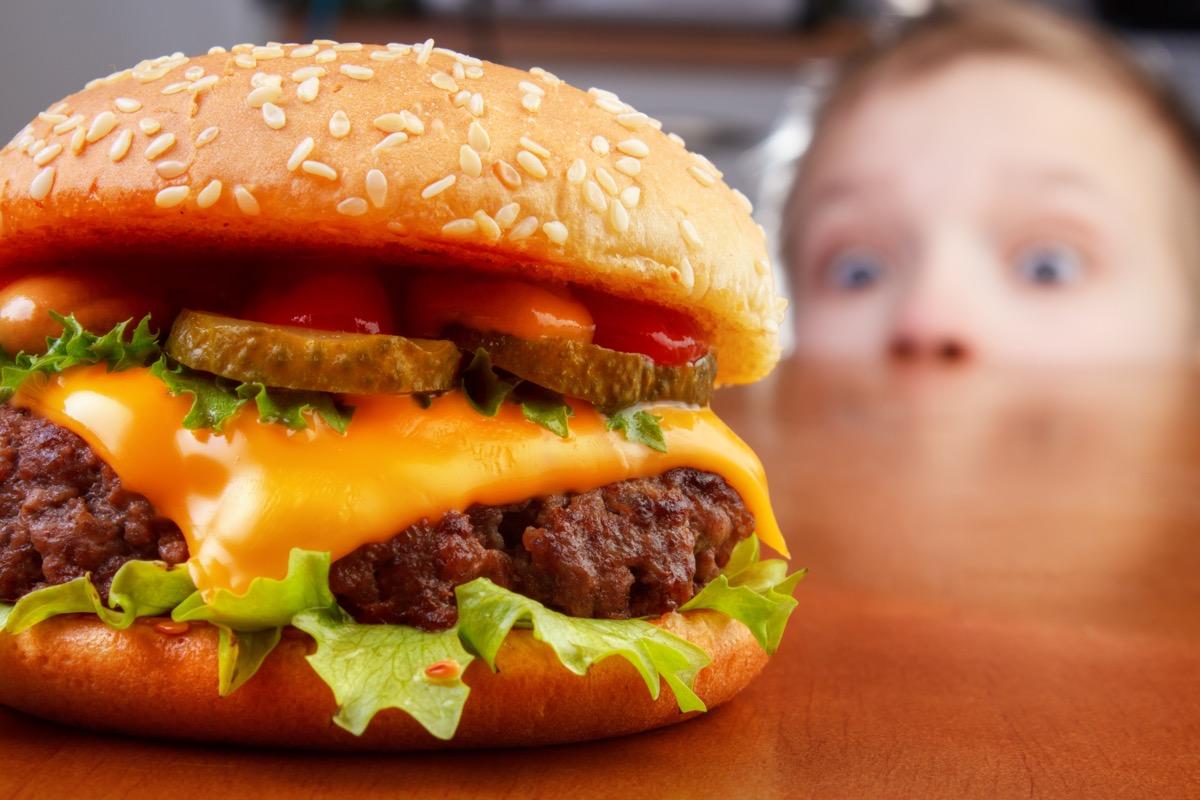 child looking at burger
