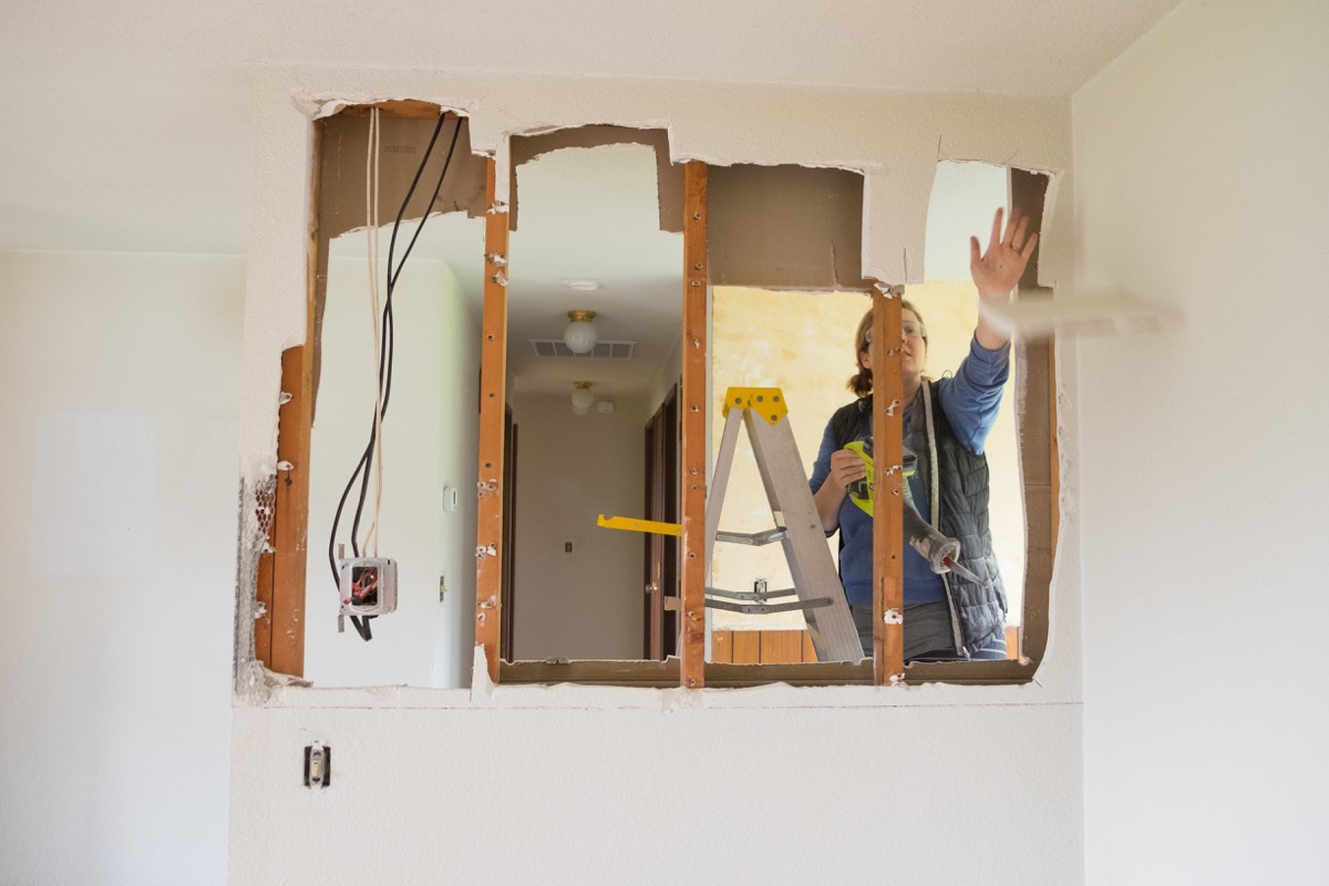 woman knocking down a wall in her house