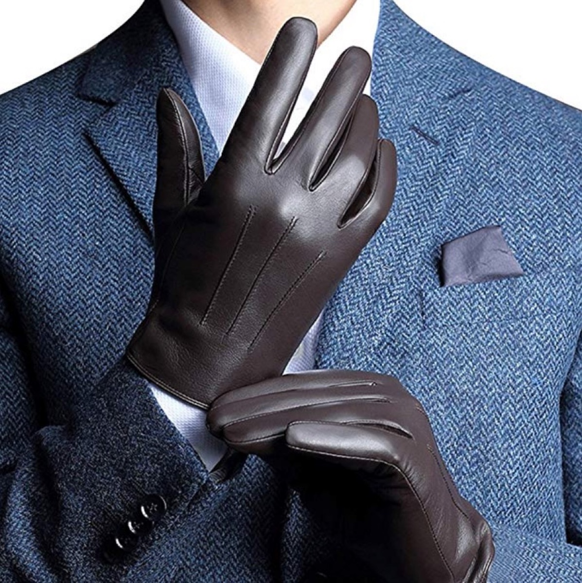 man putting on brown leather gloves