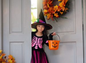 little girl in witch hat going trick or treating on halloween