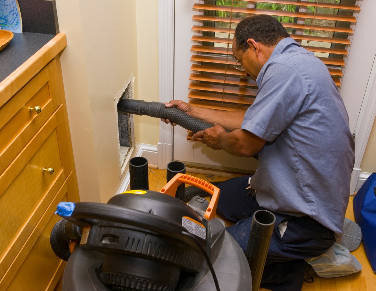 man cleaning air duct in a kitchen