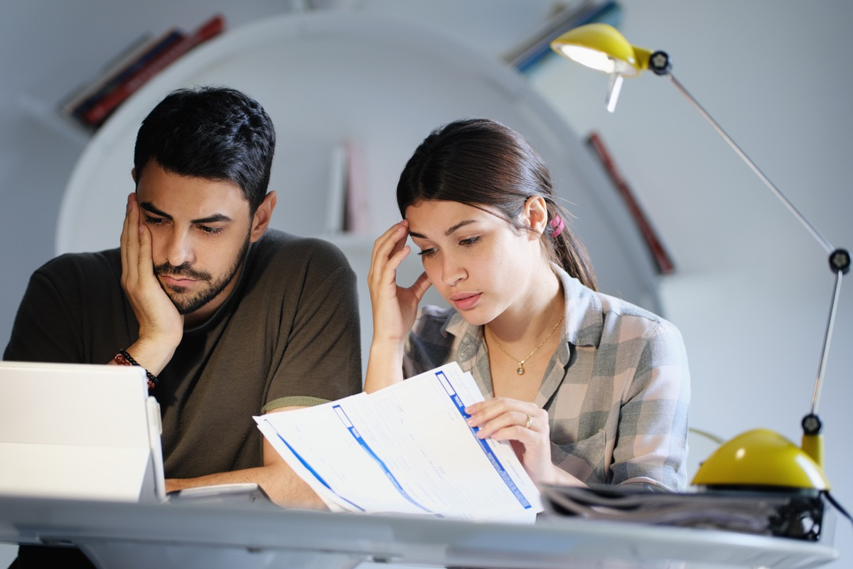 Young couple reviewing invoices and doing family business plan. Concept of money and economic problem for man and woman living together (Young couple reviewing invoices and doing family business plan. Concept of money and economic problem for man and