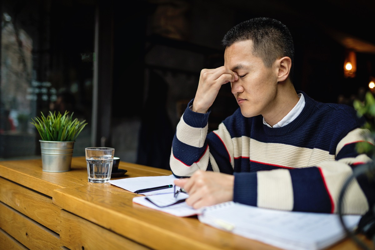 Young man feeling tired in cafe