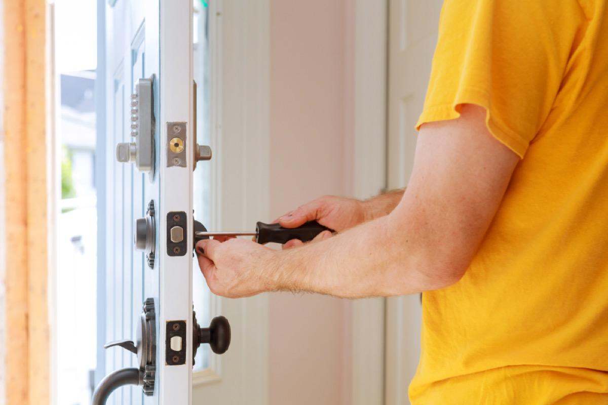 man in yellow shirt installing door lock