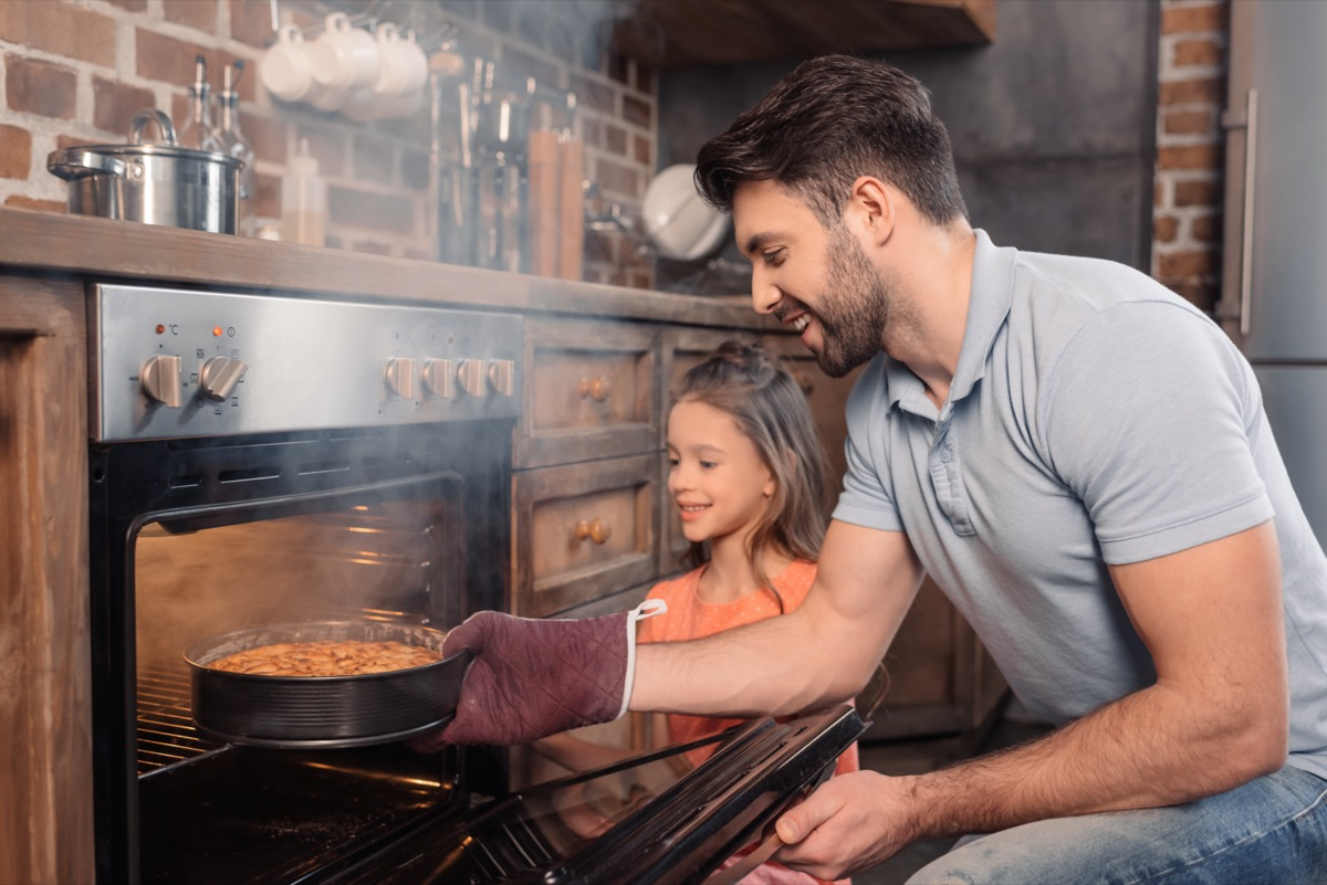 30 something white man and daughter opening steam oven