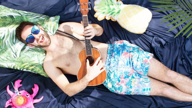 man in sugnlasses and boxers playing ukulele in bed on blue sheets