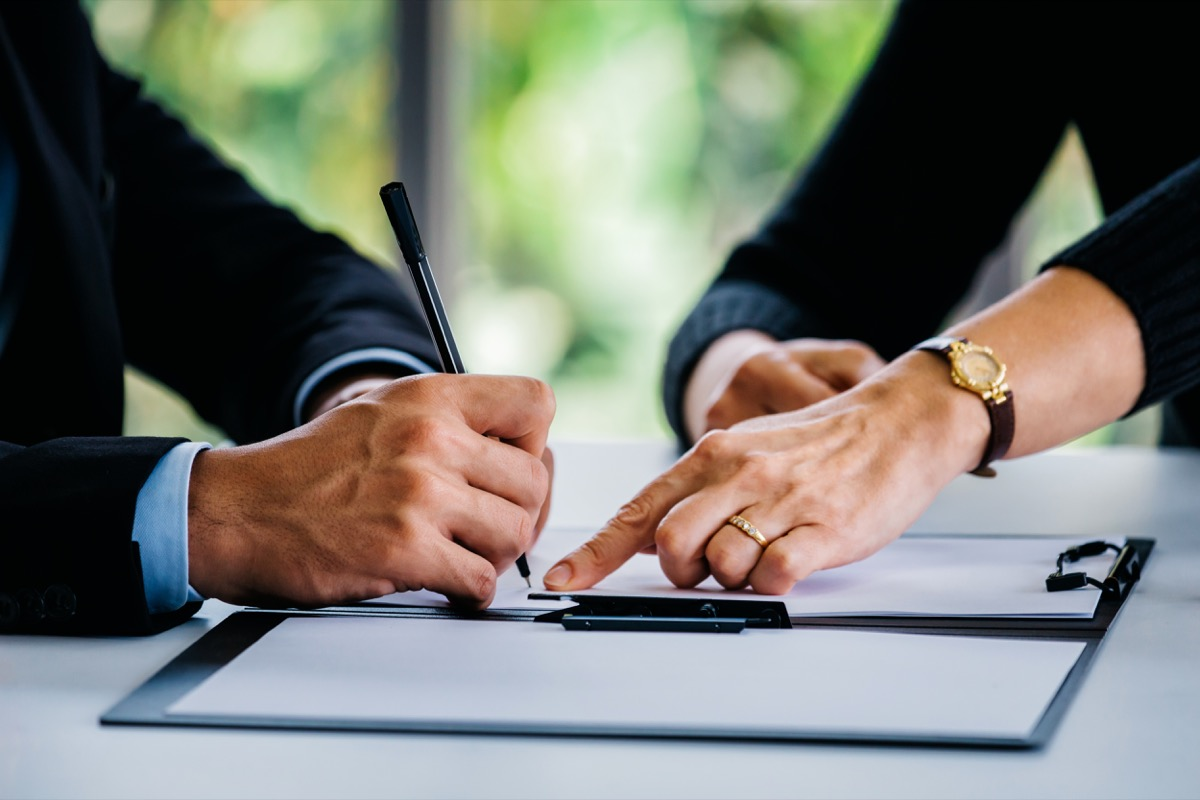 Side view of crop businesswoman pointing at contract to businessman with pen at table at office