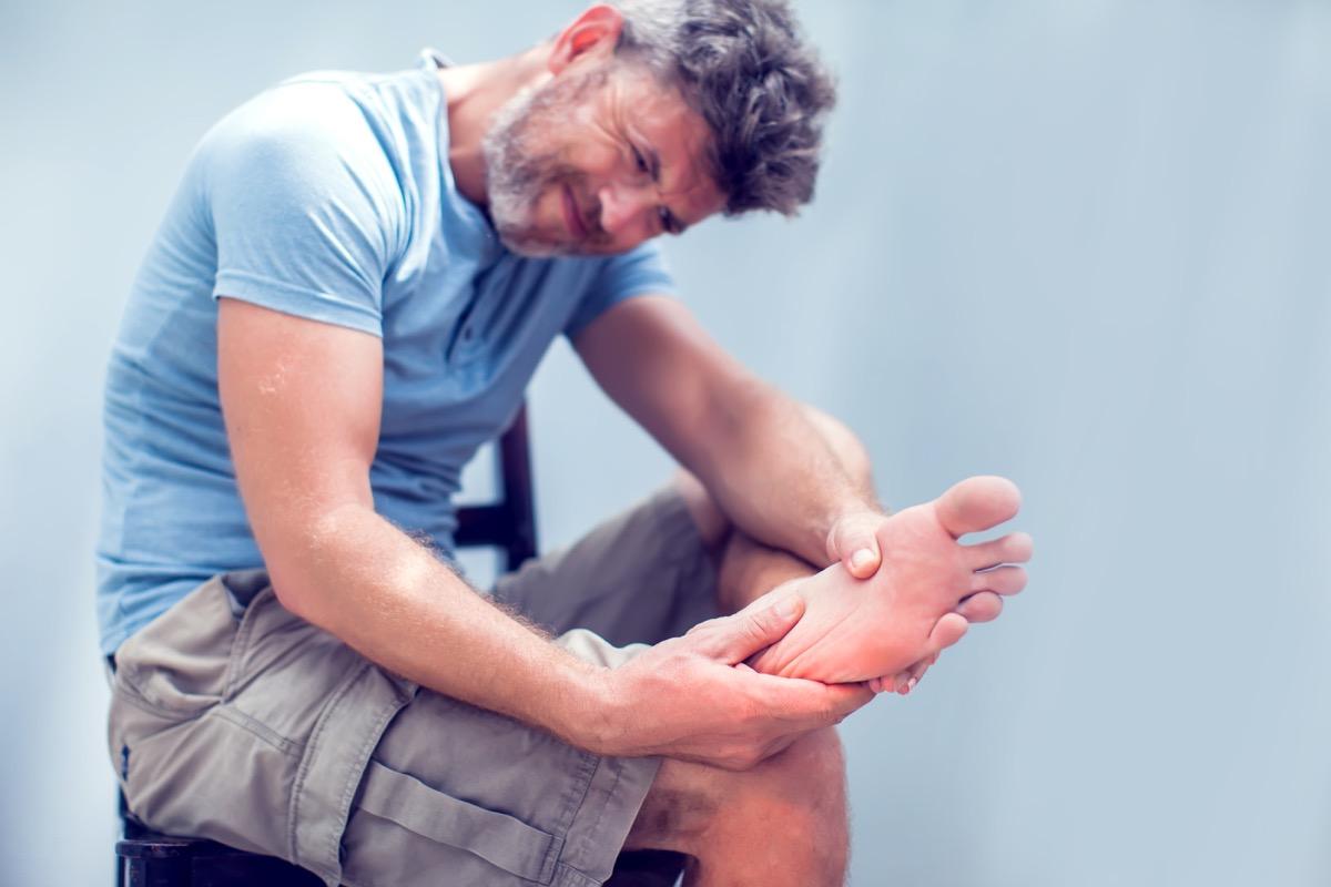 man rubbing his foot