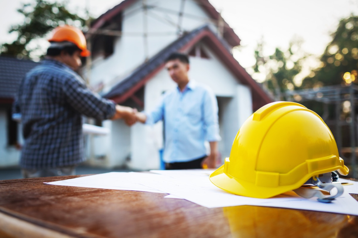 man shaking hands with a contractor outside his house