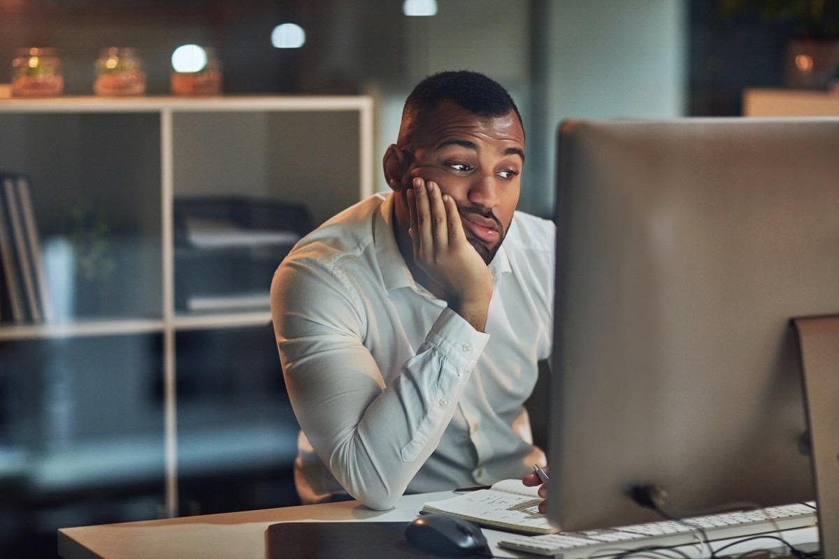 Man staring at his computer screen feeling depressed and anxious hurt mental health
