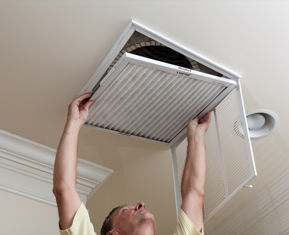 man switching out air filter in his home