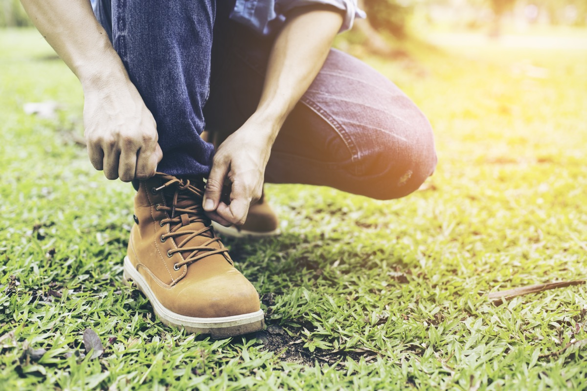man in blue jeans tying brown work boot while kneeling down on grass lawn