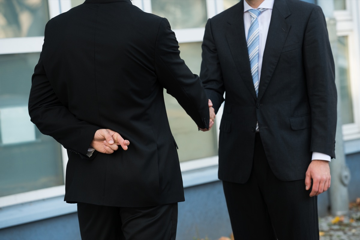 Midsection of dishonest businessman with fingers crossed shaking hands with partner outdoors