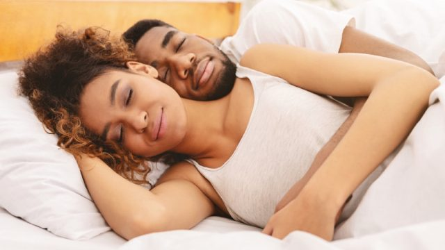 black man and woman sleeping in bed with white sheets, better sleep essentials