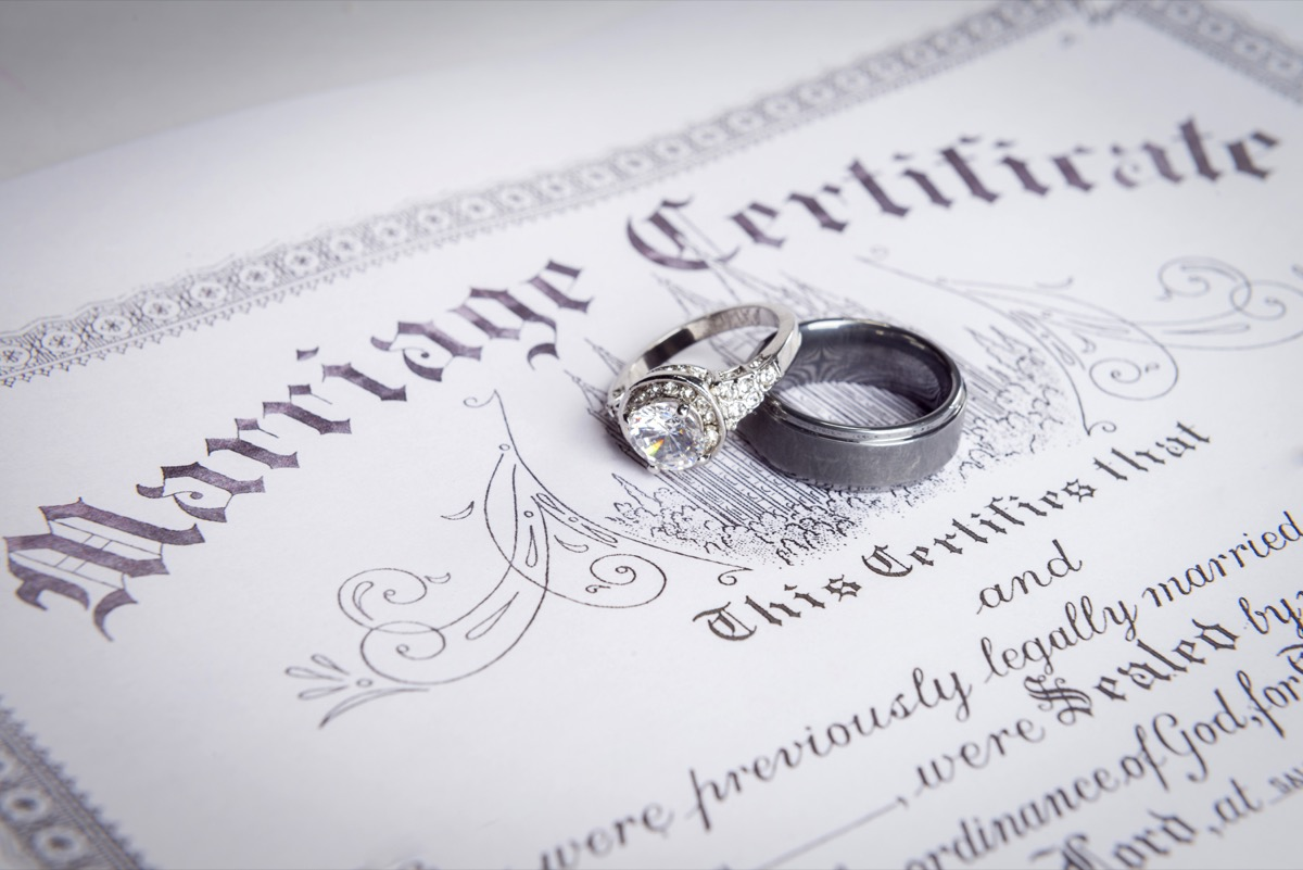 marriage certificate on the table with rings