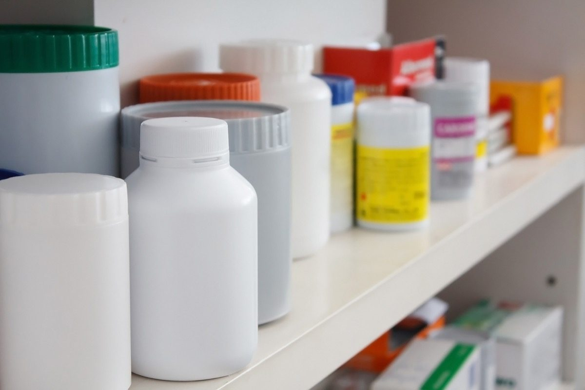 a bunch of unlabeled medicine bottles in a medicine cabinet
