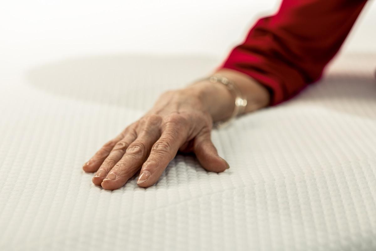 older woman placing her hand on memory foam mattress, NASA everyday items