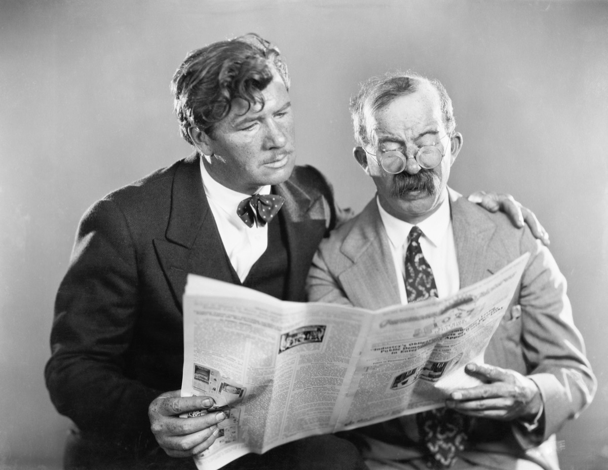 Vintage-looking photo of two men reading a newspaper