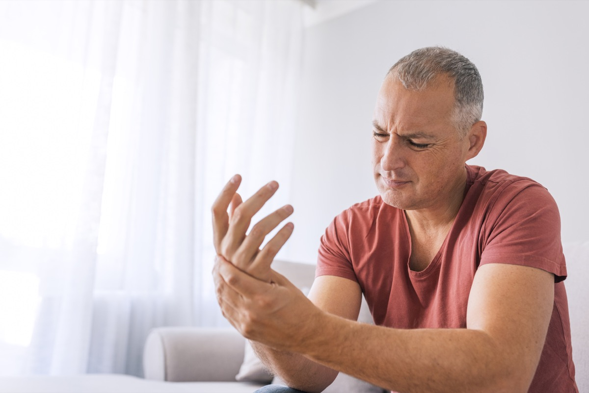 Mature man suffering from wrist pain at home while sitting on sofa during the day
