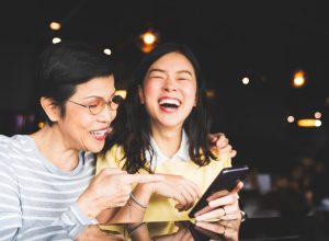 asian mother and daughter looking at a phone screen together, laughing in a cafe