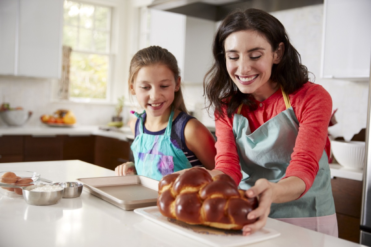 woman and young girl placing challah on kitchen counter, rosh hashanah facts