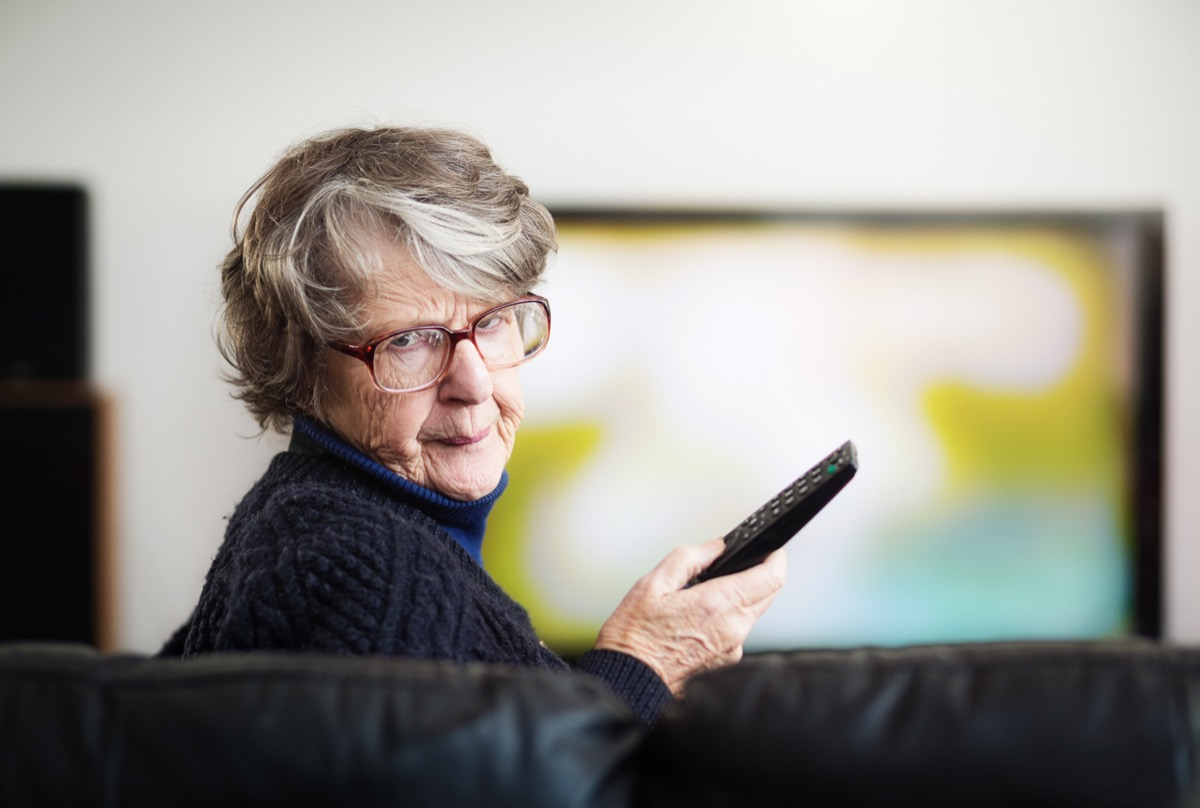 An irritated senior woman turns from the television she has been watching, holding the remote control.