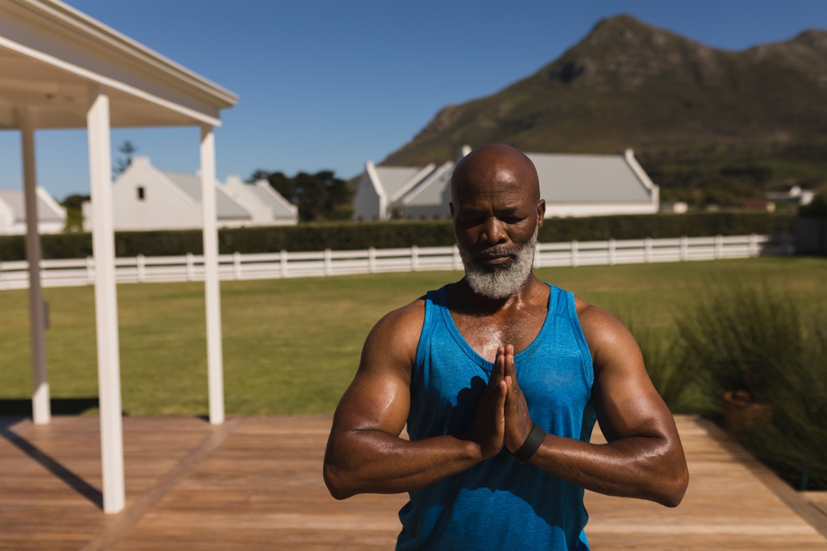 Older black man doing yoga in his backyard