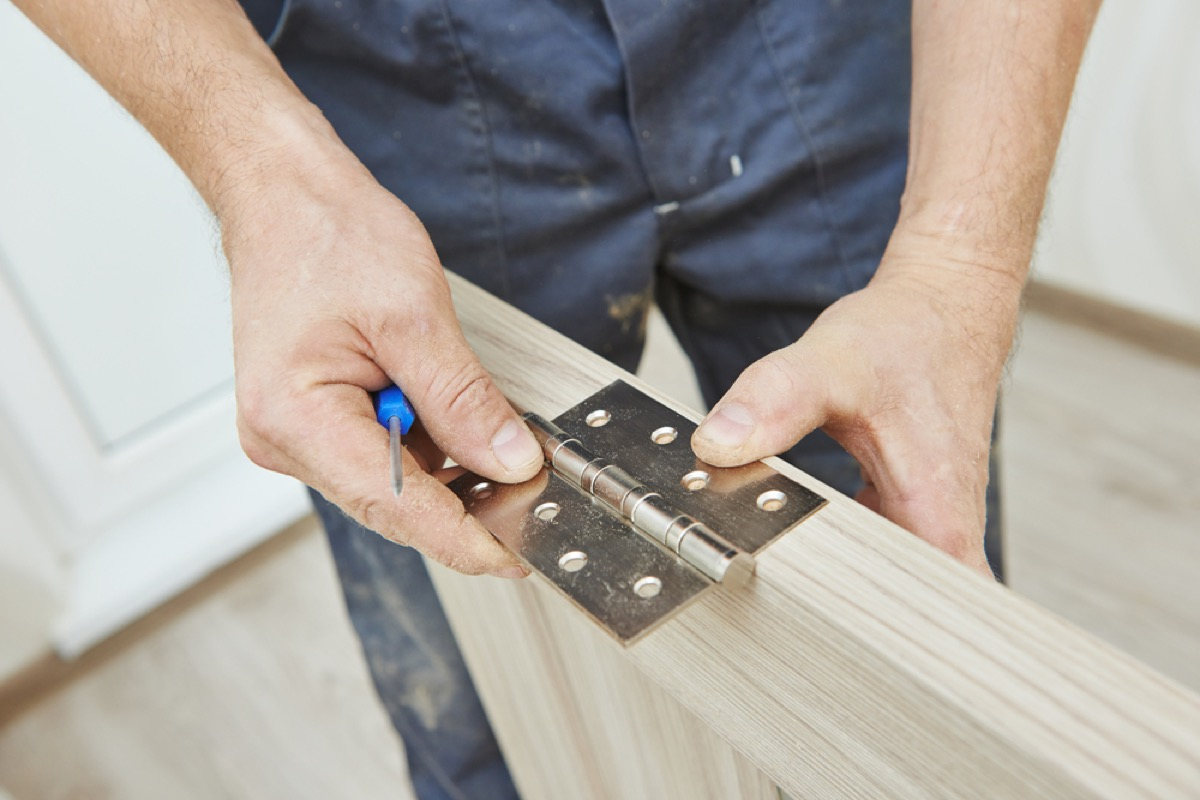 man repairing hinge on door